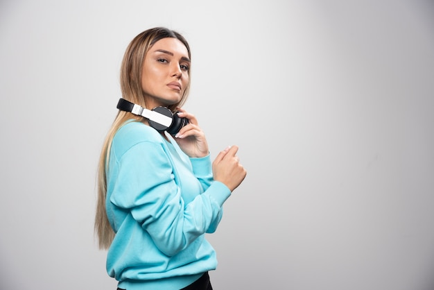 Blonde girl in blue sweatshirt posing with headphones.