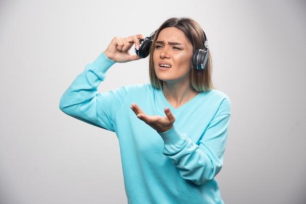 Ragazza bionda in felpa blu, tirando fuori le cuffie per ascoltare le persone intorno