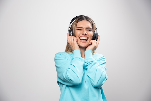 Blonde girl in blue sweatshirt wearing headphones, enjoying the music and having fun.
