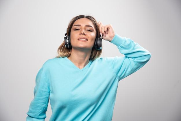Ragazza bionda in felpa blu che indossa le cuffie, godersi la musica e divertirsi