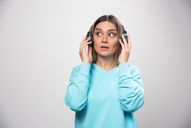 Blonde girl in blue sweatshirt wearing headphones and trying to understand the music