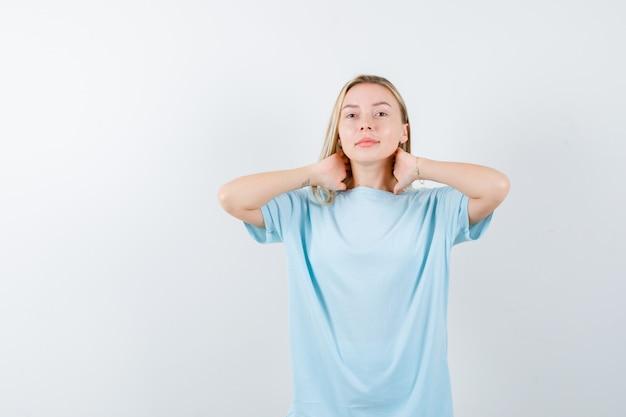 Ragazza bionda in maglietta blu che tiene le mani sul collo e che sembra serio, vista frontale.