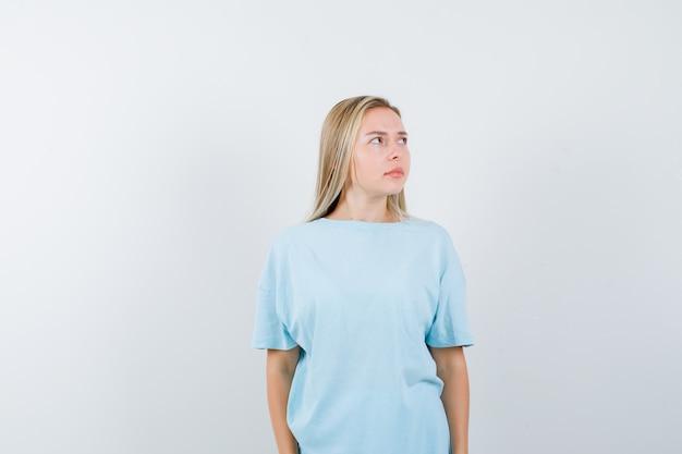 Ragazza bionda in maglietta blu che guarda lontano mentre posa alla macchina fotografica e sembra carina, vista frontale.
