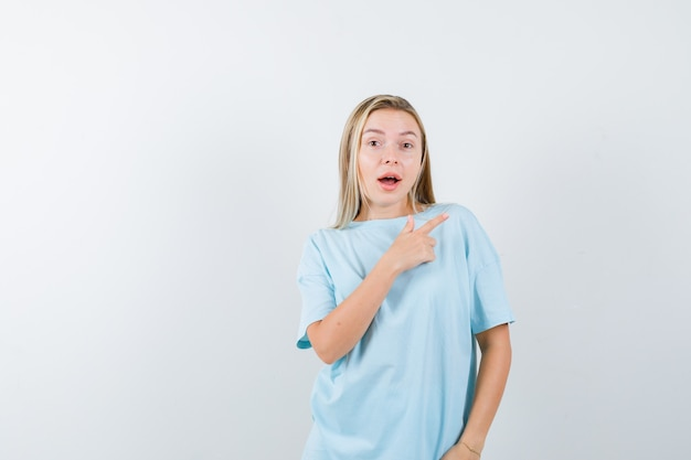 Blonde girl in blue t-shirt pointing right with index finger and looking surprised , front view.