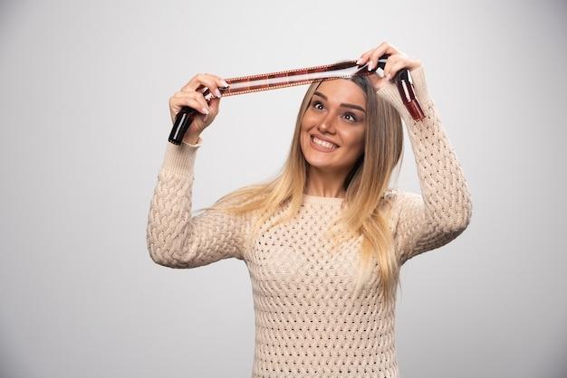 사진 롤에서 사진을 확인하는 금발 소녀는 결과에 대해 행복하고 긍정적입니다.