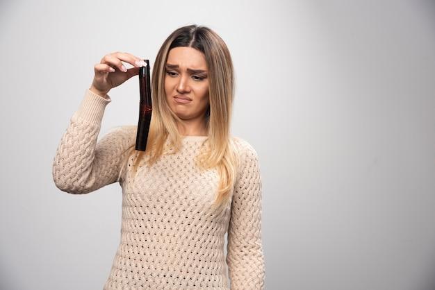 Ragazza bionda che controlla le foto sul rullino fotografico e si sente delusa.