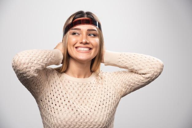 Ragazza bionda che controlla le foto su pellicola polaroid e si sente felice e positiva per il risultato