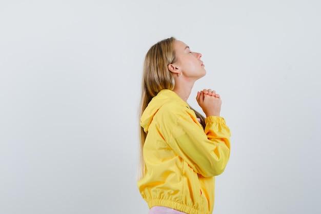 Tシャツ、ジャケットで祈りのジェスチャーで手を握りしめ、希望に満ちたブロンドの女の子。 。