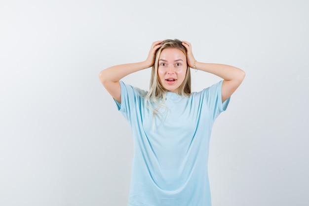 Ragazza bionda che stringe la testa con le mani in maglietta blu e sembra carina. vista frontale.