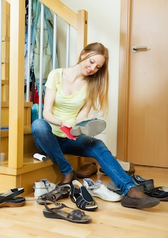 Blonde girl cleaning shoes