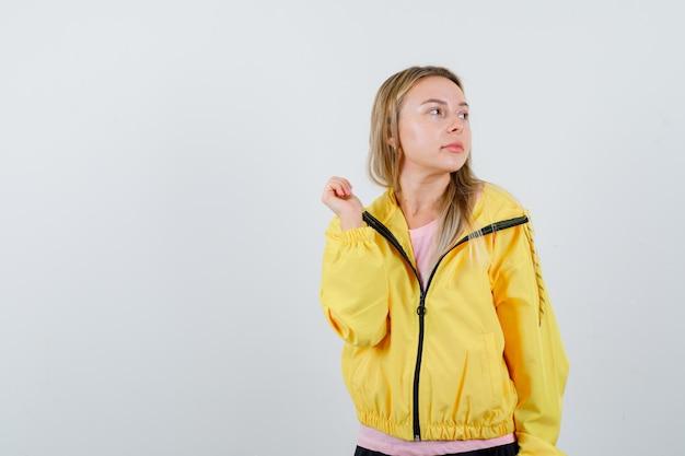 금발 소녀 주먹을 움켜 쥐고 분홍색 티셔츠와 노란색 재킷을 입고 매혹적인 찾고