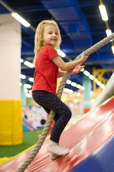 Blonde girl climbing a rope