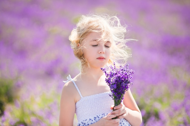 Blonde girl in the colour dress in the field of lavander with a small bouqet in her hands