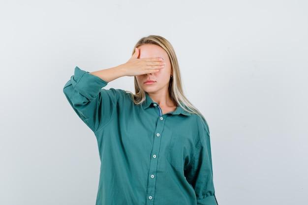 Ragazza bionda che copre l'occhio con la mano in camicetta verde e sembra seria