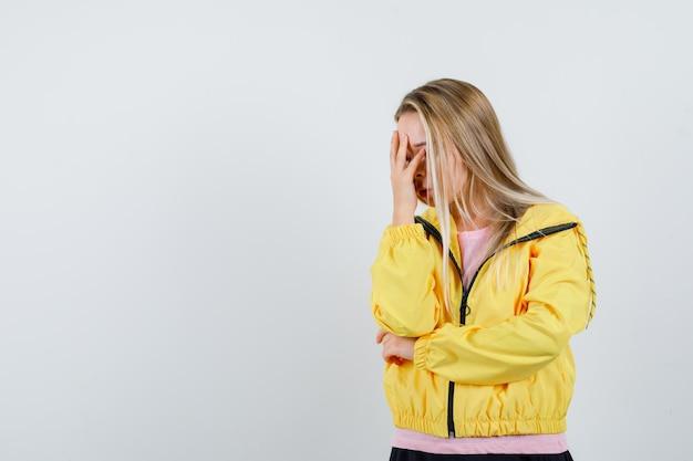 ピンクのtシャツと黄色のジャケットで手で顔を覆ってイライラしているブロンドの女の子