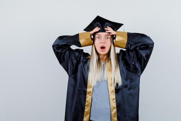 手で頭を覆い、卒業式のガウンとキャップで口を開けて驚いたブロンドの女の子。