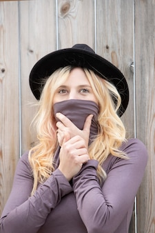 Блондинка закрывает рот футболкой на открытом воздухе девушка в очках и шляпе
