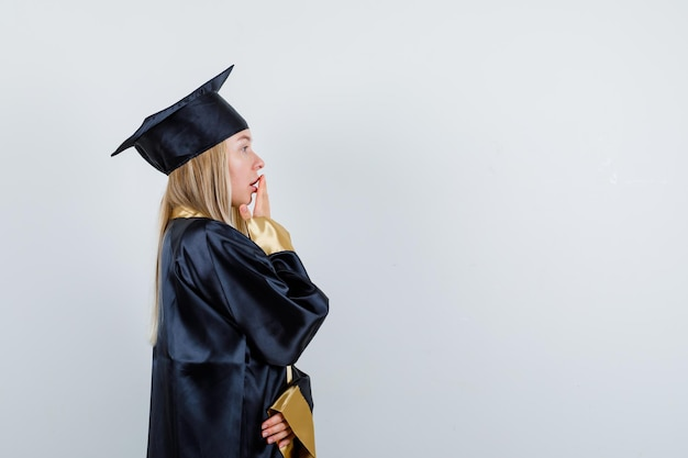 Blonde girl covering mouth with hand in graduation gown and cap and looking surprised.