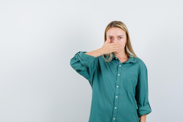 Ragazza bionda che copre la bocca con la mano in camicetta verde e sembra seria