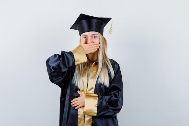 Ragazza bionda che copre la bocca con la mano mentre tiene la mano sulla pancia in abito da laurea e berretto e sembra sorpresa