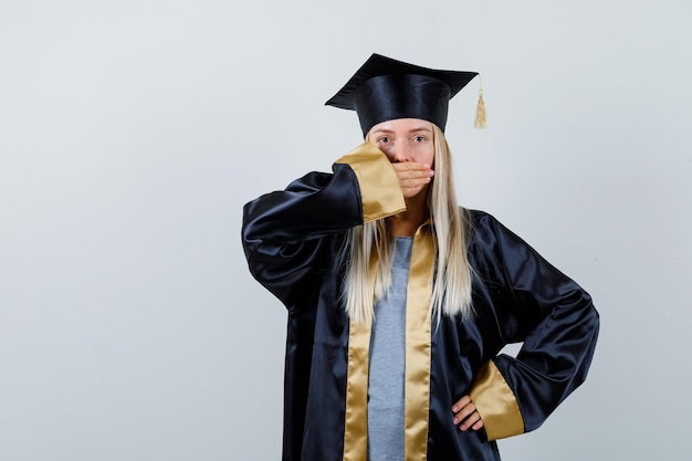 卒業式のガウンとキャップで腰に手を握り、驚いて見えるように手で口を覆っているブロンドの女の子。