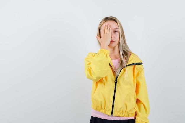 Ragazza bionda che copre parte del viso con la mano in maglietta rosa e giacca gialla e sembra seria.