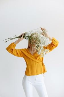 ブロンドの女の子は乾いた白い花で彼女の顔を覆います。ロマンス。ブロガー、初秋