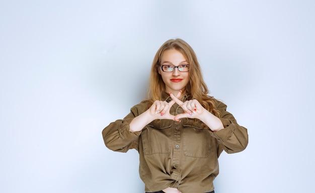 손가락을 건너고 삼각형을 만드는 금발 소녀.