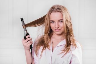 彼女の髪をカーリングブロンドの女の子