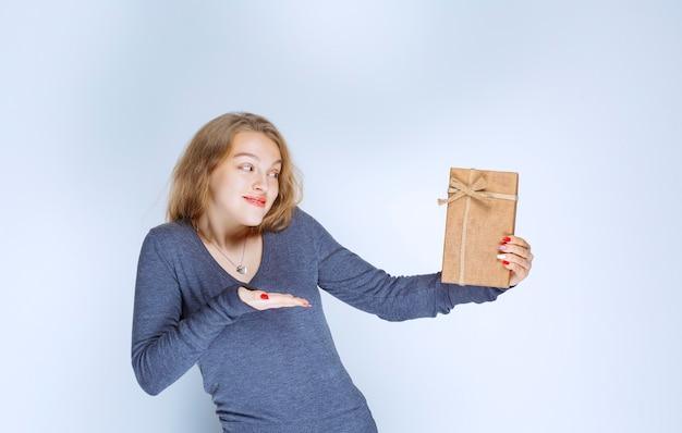 Блондинка демонстрирует свою картонную подарочную коробку и чувствует себя позитивно.