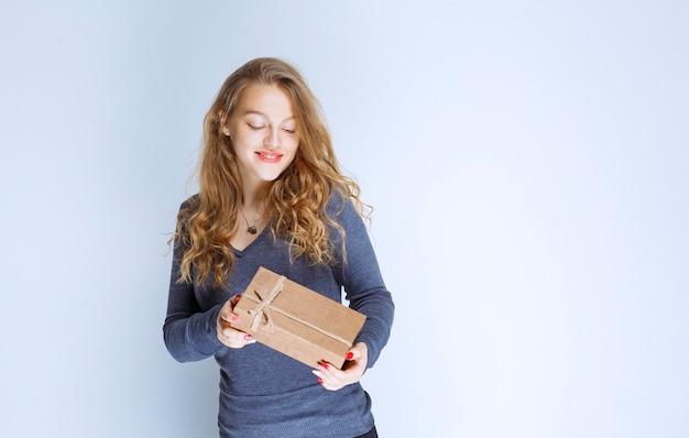 Blonde girl demonstrating her cardboard gift box and feeling positive.