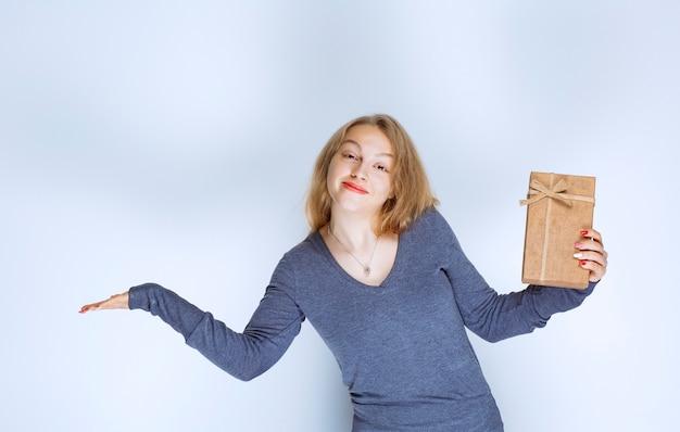 Ragazza bionda che dimostra la sua confezione regalo di cartone e si sente positiva.