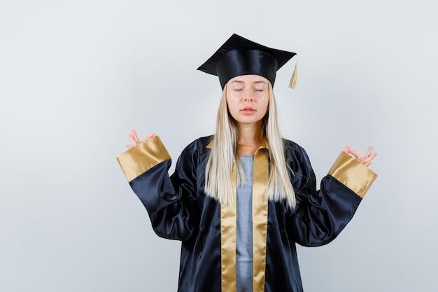 Ragazza bionda che fa meditazione con gli occhi chiusi in uniforme laureata e sembra piena di speranza
