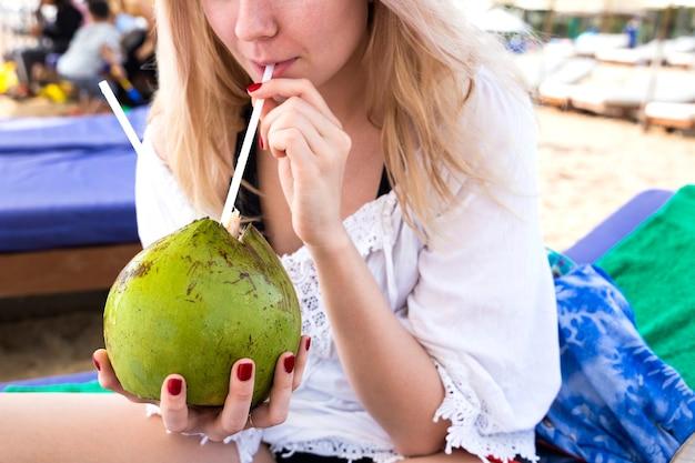 ブロンドの女の子はビーチでココナッツから飲む