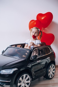Blonde girl eating a caramel lollypop in the shape of a heart. kid sitting in a black toy car with red heart shaped balloons.valentine's day concept.