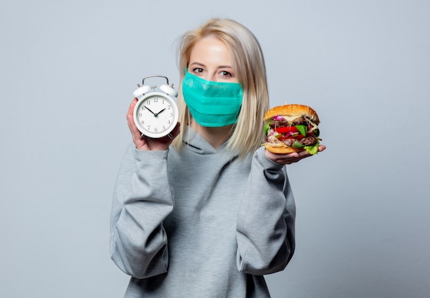Blonde girl in face mask with burger and alarm clock on white space