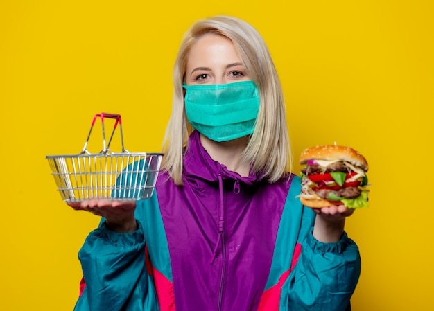 Blonde girl in face mask with burger and shopping basket