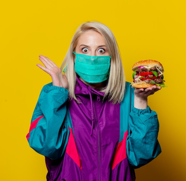 Blonde girl in face mask with burger