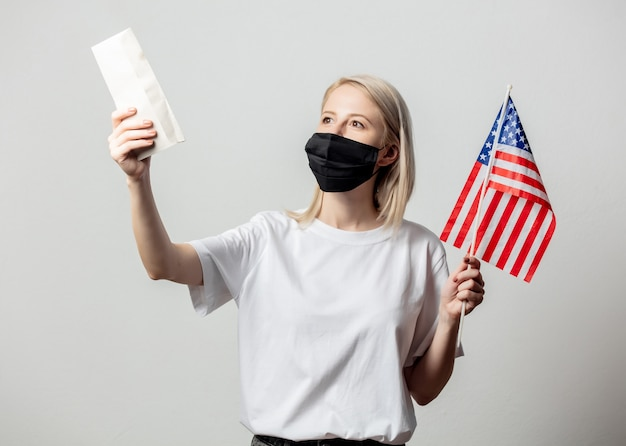 Blonde girl in face mask with usa flag and money