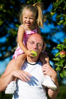 Blonde girl feeding daddy with apple