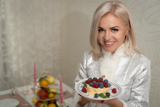 A blonde girl in a festive dress holds a dessert decorated with berries in her hands