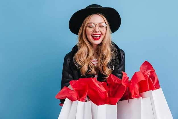 Blonde girl in glasses holding shopping bags. attractive female shopaholic posing on blue wall.