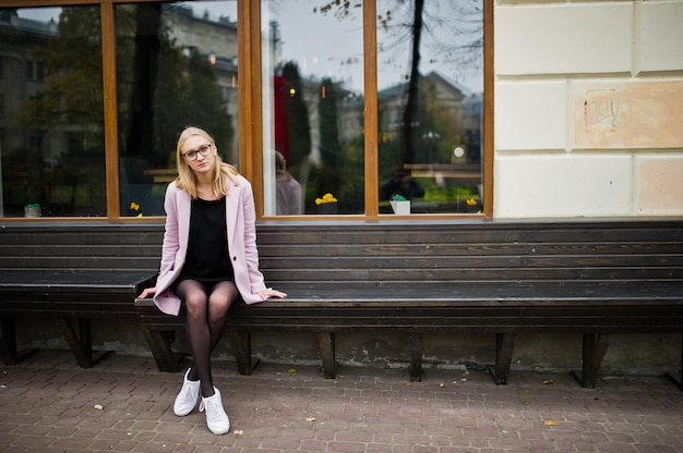 Blonde girl at glasses and pink coat, black tunic sitting on bench at street.