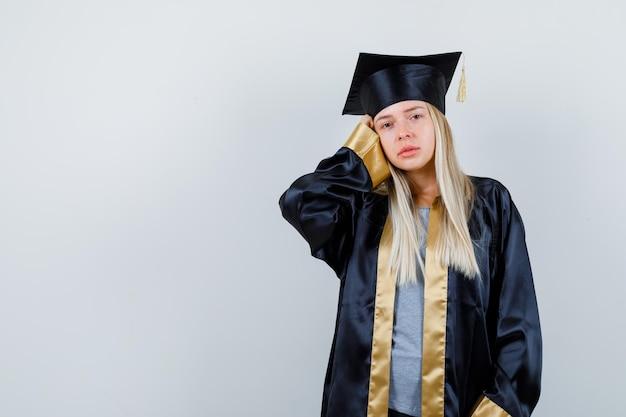 Ragazza bionda in uniforme laureata che tiene la mano sulla testa e sembra addolorata