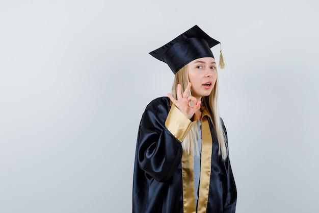 Ragazza bionda in uniforme laureata che mostra gesto ok e sembra sicura