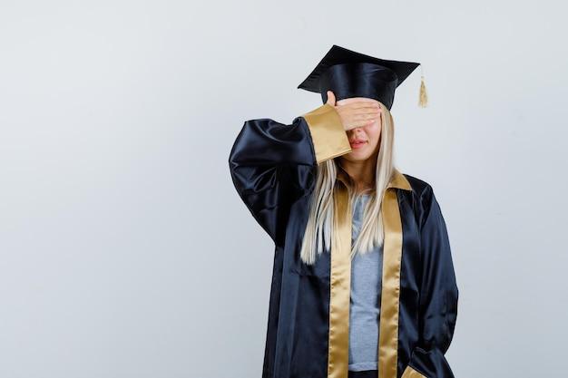 Ragazza bionda in abito da laurea e berretto che copre gli occhi con la mano e sembra seria