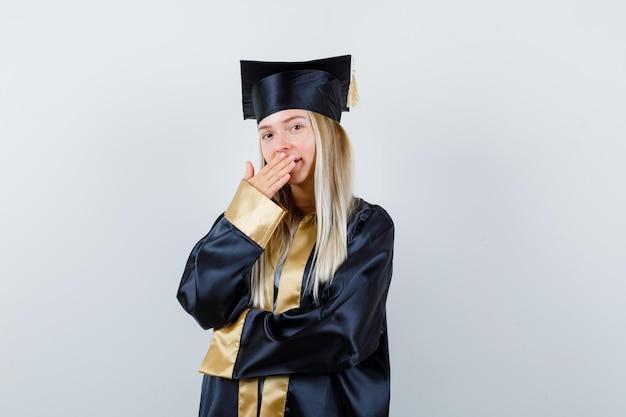 Ragazza bionda in abito da laurea e berretto che copre la bocca con la mano e sembra sorpresa