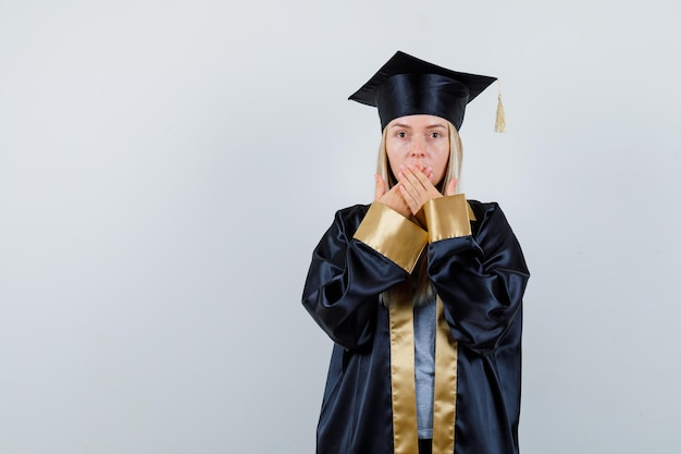 Blonde girl in graduation gown and cap covering mouth with hands and looking surprised