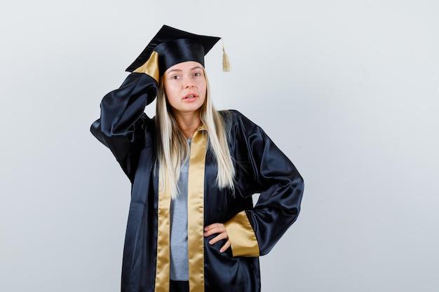 Ragazza bionda in abito da laurea e berretto che tiene la mano sulla vita, mette la mano sulla testa e sembra sicura