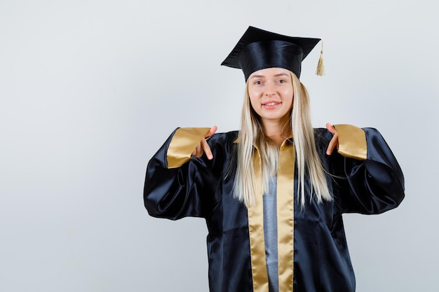 Ragazza bionda in abito da laurea e berretto rivolto verso il basso con l'indice e dall'aspetto carino